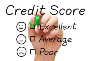 Hand putting check mark with green marker on excellent credit score evaluation form.